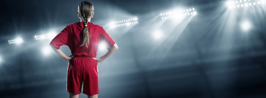 Young girl in a soccer uniform stands confidently with hands on hips in a stadium environment