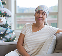 patient in head scarf sitting near Christmas tree.
